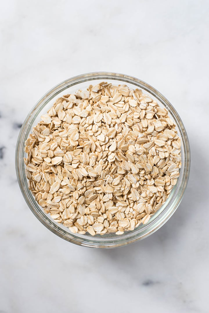 Overhead image of a glass bowl filled with rolled oats for the Overnight Oats recipe.