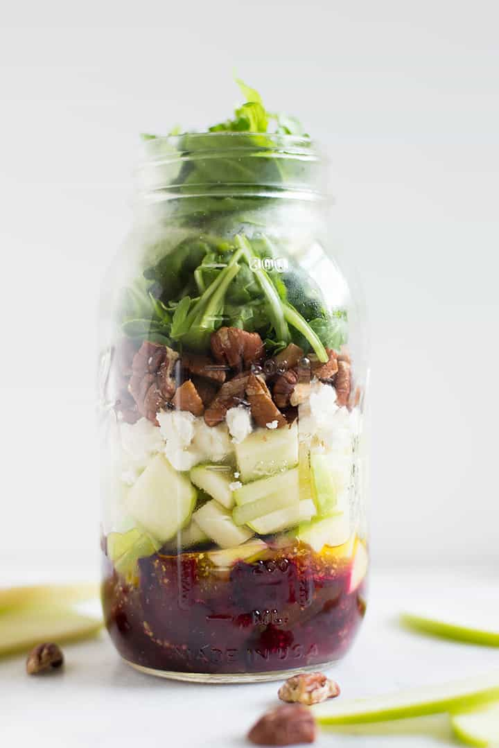 1 quart size mason jar salad filled with beet and goat cheese salad to show how to stack the mason jar salad,starting with dressing on bottom and the arugula leaves on top