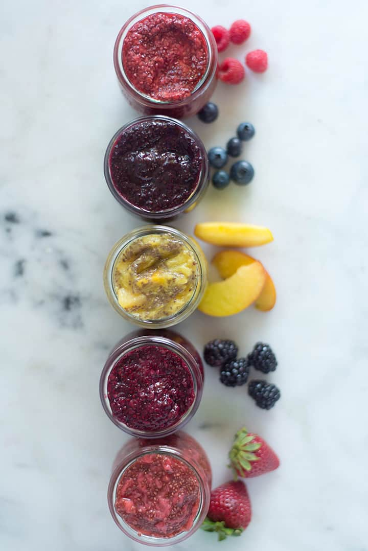 An overhead image of 5 glass jars on a kitchen counter, each filled with Homemade Chia Jam including Homemade Raspberry Chia Jam, Homemade Blueberry Chia Jam, Homemade Peach Chia Jam, Homemade Blackberry Chia Jam and Homemade Strawberry Chia Jam.