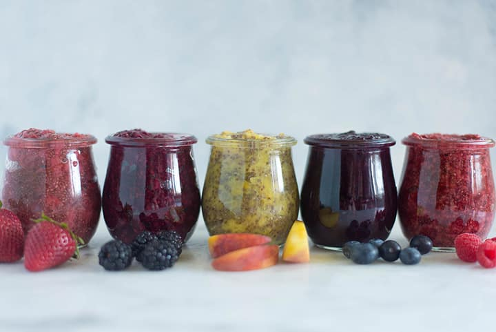 A side image of 5 glass jars on a kitchen counter, each filled with Homemade Chia Jam, including Homemade Strawberry Chia Jam, Homemade Blackberry Chia Jam, Homemade Peach Chia Jam, Homemade Blueberry Chia Jam and Homemade Raspberry Chia Jam.