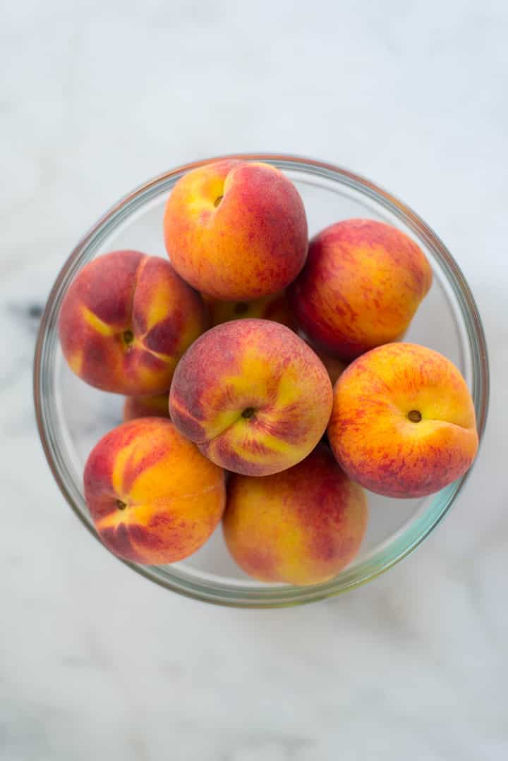 An overhead image of a bowl of fresh, whole peaches ready for the Homemade Peach Chia Jam.
