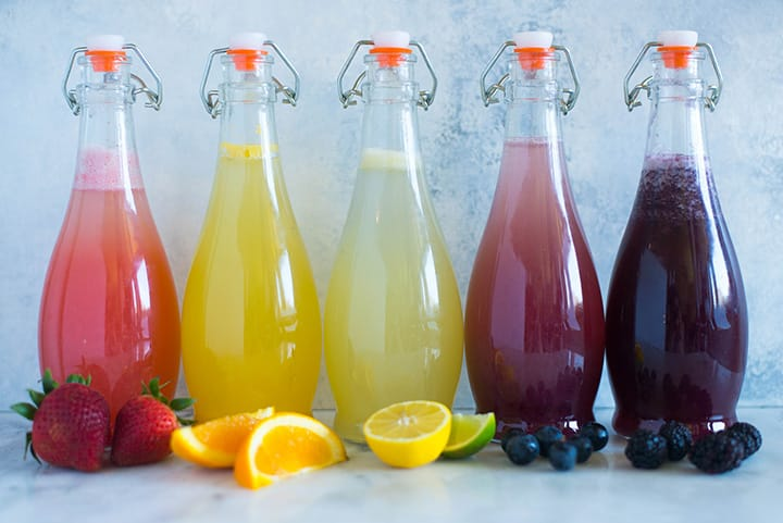 A side image of five sealed glass bottles on a kitchen counter with Caffeine-free Homemade soda, including Strawberry Soda, Orange Soda, Lemon Lime Soda, Grape Soda and Blackberry Soda.