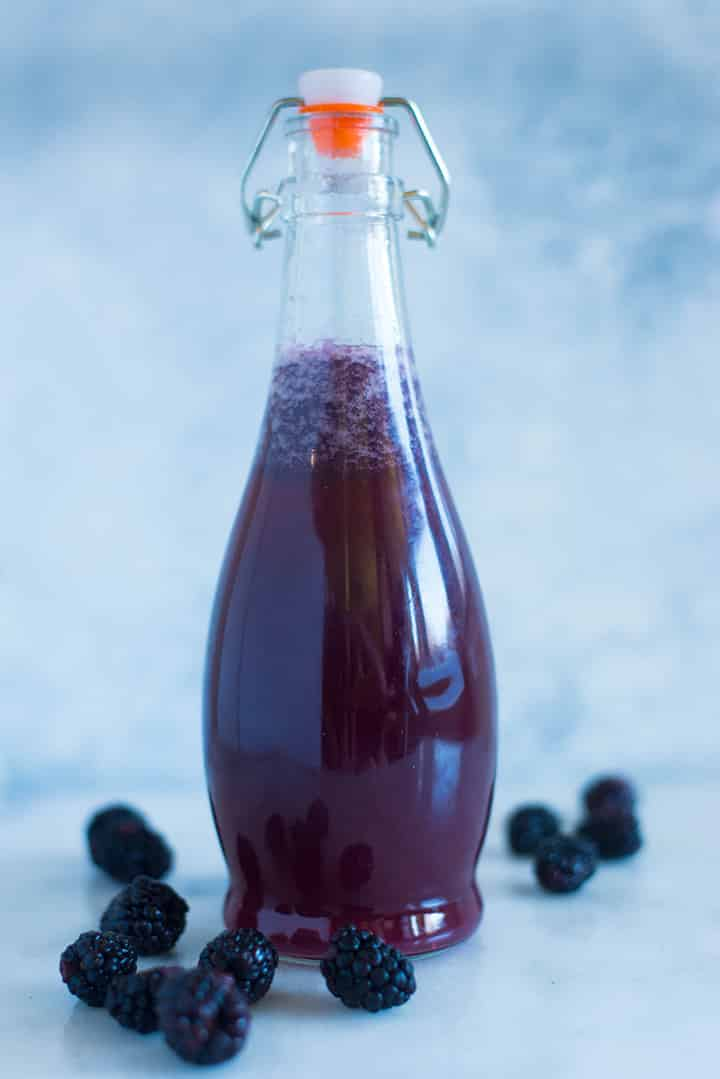 A side image of a sealed glass bottle with Caffeine-free Homemade Blackberry Soda made from fresh blackberries, raw honey simple syrup and seltzer water.