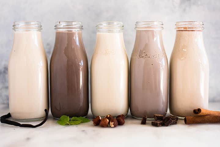A side image of 5 glass bottles lined up on the kitchen counter, each filled with one Healthy Homemade Coffee Creamer including Homemade Cinnamon Creamer, Homemade Chocolate Creamer, Homemade Hazelnut Creamer, Homemade Peppermint Mocha Creamer and Homemade French Vanilla Creamer.