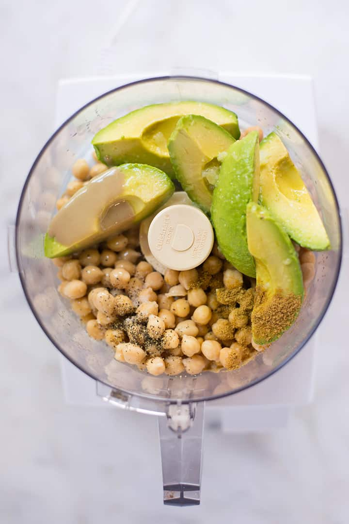 An overhead image of a food processor with all the ingredients for Avocado Hummus including drained canned chickpeas, avocado slices, a clove of garlic, tahini, cumin, olive oil, fresh lime juice, salt and ground black pepper.