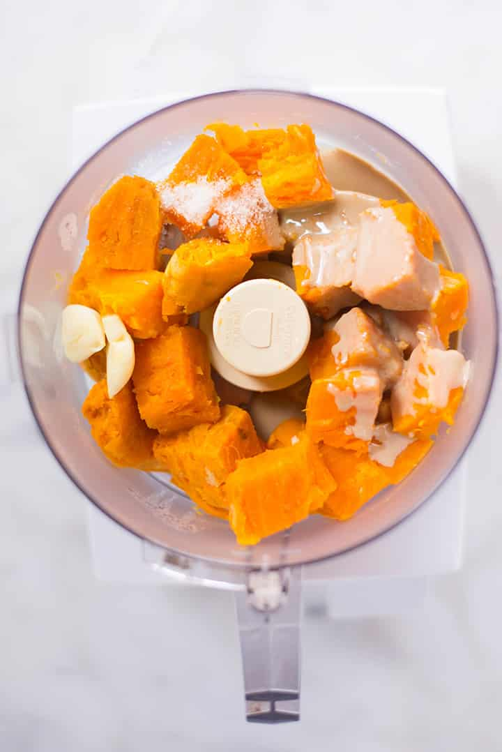 An overhead image of a food processor with the ingredients for the Sweet Potato Hummus including a large sweet potato, peeled and cut into large pieces, 2 cloves of garlic, pure tahini, sea salt and lemon juice.