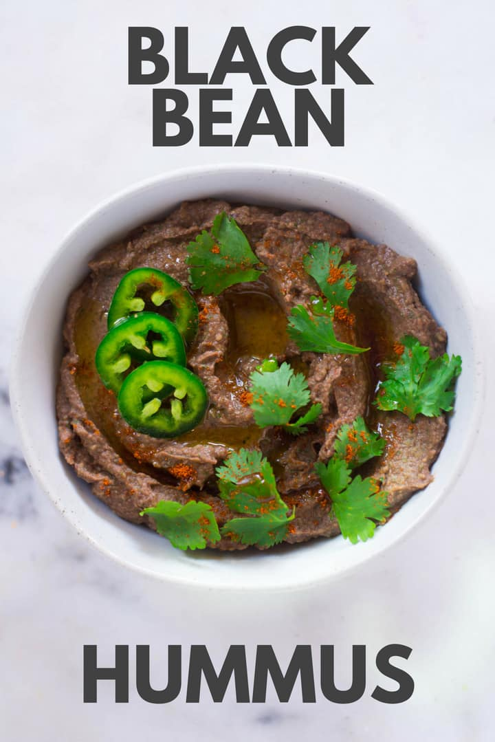 An overhead image of a bowl of Homemade Black Bean Hummus made from black beans, jalapeno pepper, garlic, cilantro, cumin, paprika, extra virgin olive oil, lime juice and sea salt garnished with slices of jalapeno pepper, cilantro and cayenne.