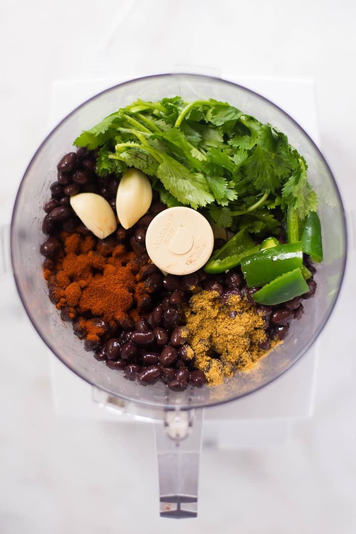 An overhead image of a food processor with all the ingredients for Black Bean Hummus including drained and rinsed black beans, diced jalapeno pepper, two garlic cloves, cilantro, cumin, paprika, extra virgin olive oil, lime juice and sea salt.