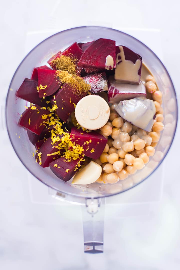 An overhead image of a food processor with all the ingredients for Beet Hummus including cooked, cubed beets, drained canned chickpeas, one garlic clove, tahini, ground cumin, lemon zest and sea salt.