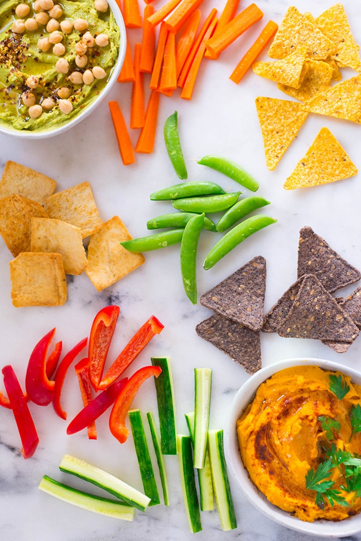 An overhead image of two large servings of Homemade Hummus including a bowl of Avocado Hummus garnished with chickpeas and red pepper flakes and a bowl of Sweet Potato Hummus garnished with fresh parsley, and an array of dipping options laid out on the table including carrot sticks, cucumber sticks, sliced bell peppers, green beans, edamame, black bean chips, simple naked pita chips and tortilla chips.