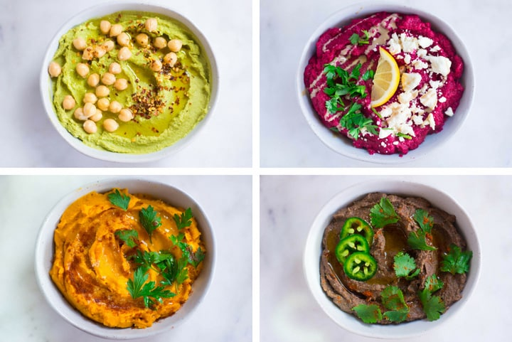 An overhead image of four glass bowls, each containing a different kind of Homemade Hummus including a bowl of Avocado Hummus, garnished with chickpeas and red pepper flakes, a bowl of Beet Hummus garnished with crumbled feta cheese and fresh parsley, a bowl of Sweet Potato Hummus garnished with fresh parsley and a bowl of Black Bean Hummus garnished with cilantro, jalapenos and cayenne.