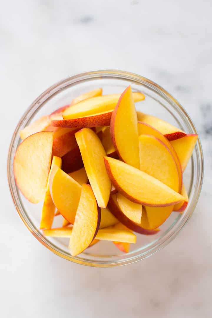 An overhead image of a glass bowl of fresh peach slices ready for Peach Sorbet.