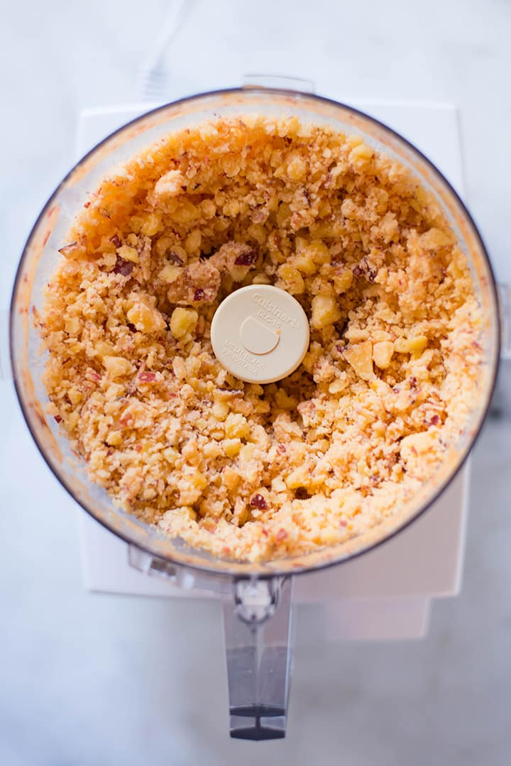 An overhead image of a food processor with processed frozen peaches ready for the Peach Sorbet.