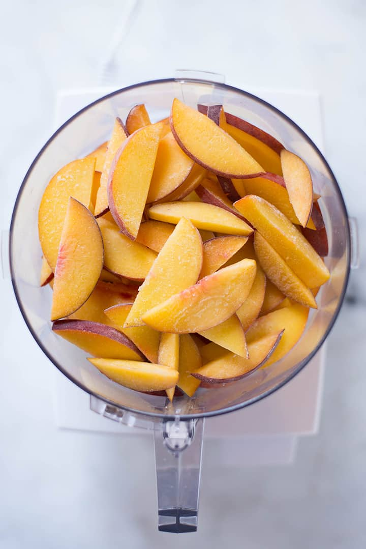 An overhead image of a food processor with frozen peach slices ready to be processed for the Peach sorbet.