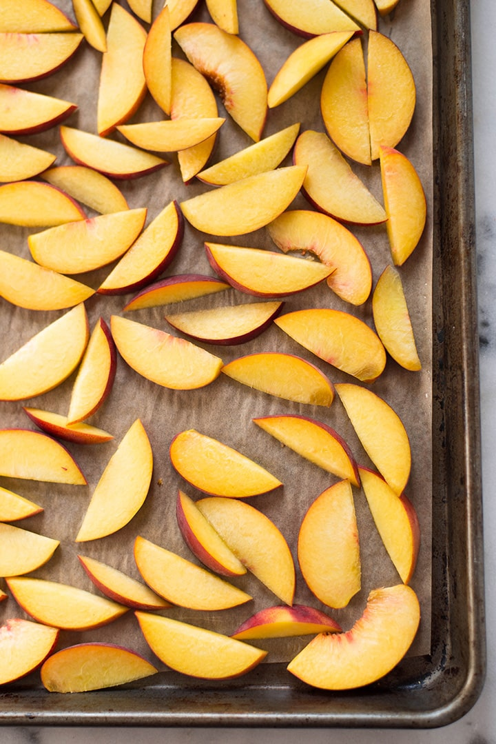 An overhead image of peach slices placed on a cookie sheet ready for freezing for the Peach Sorbet.