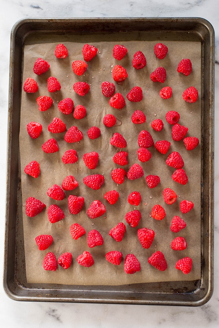 An overhead image of fresh raspberries on a cookie sheet ready for freezing and making into raspberry sorbet.
