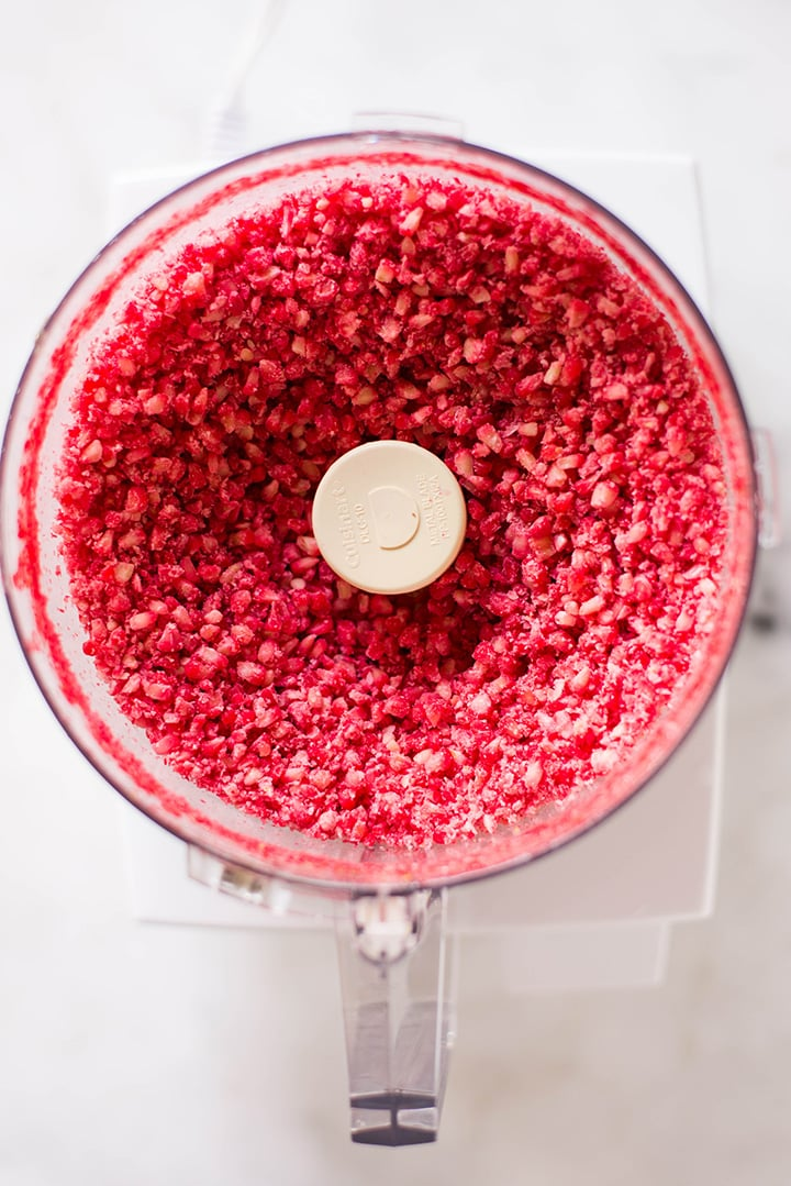 An overhead image of a food processor with processed fresh raspberries for the Raspberry Sorbet.