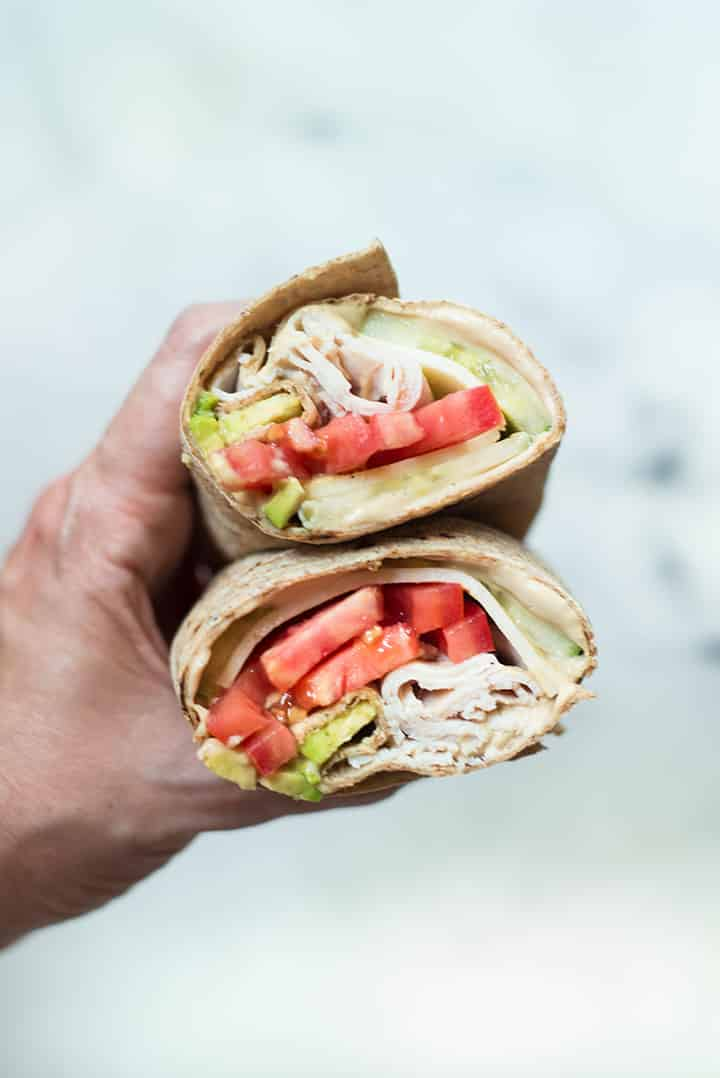 A close up of a hand holding an Avocado Turkey Hummus Wrap sliced in half made with smoked deli turkey breast, hummus, avocado, muenster cheese, cucumber slices and roma tomatoes wrapped in a whole wheat tortilla.