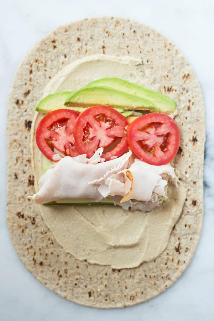 Avocado Turkey Hummus Wrap laid out and ready to roll up into a wrap, showing how to place everything onto the wrap.