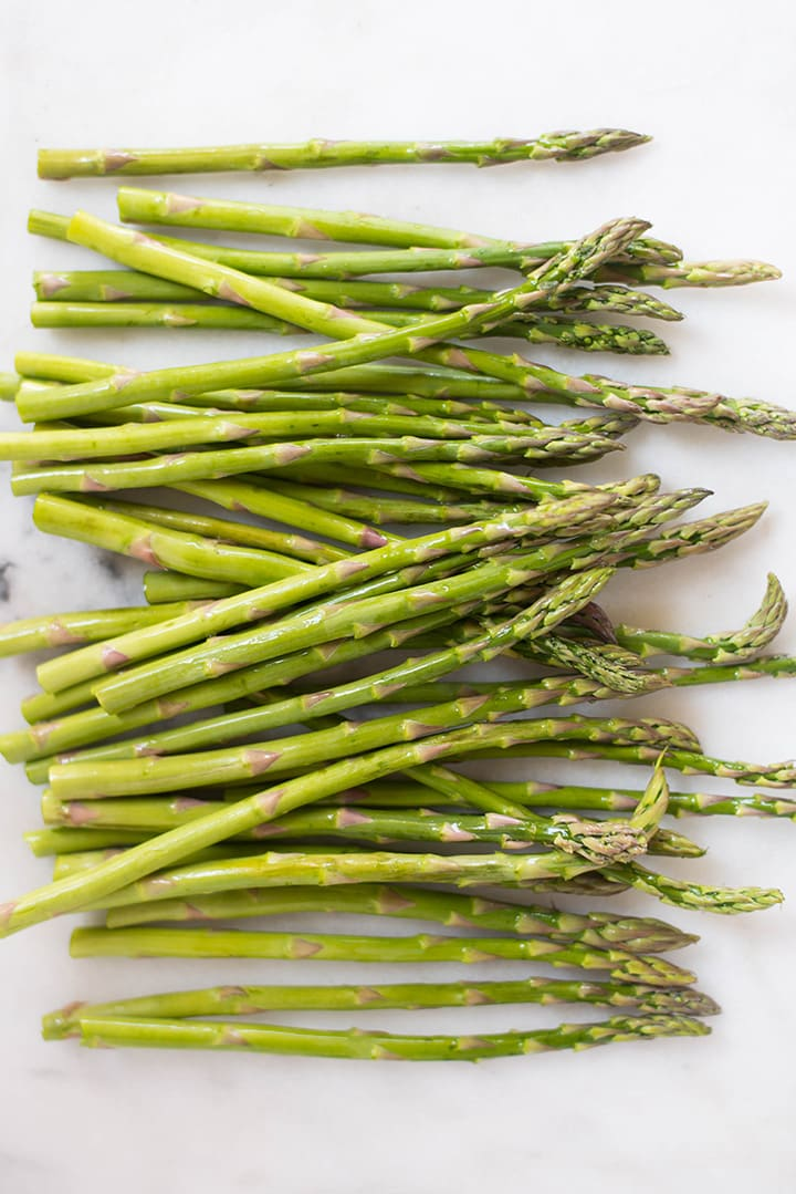An overhead image of fresh asparagus stalks on a kitchen counter, for the Oven Baked Parmesan Asparagus Fries