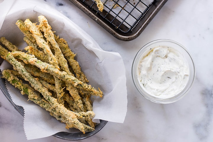 An overhead image of a serving tray with Oven Baked Parmesan Asparagus Fries made with fresh asparagus, almond meal, grated parmesan, chickpea flour, eggs, freshly ground black pepper and sea salt, served with a dip on the side.