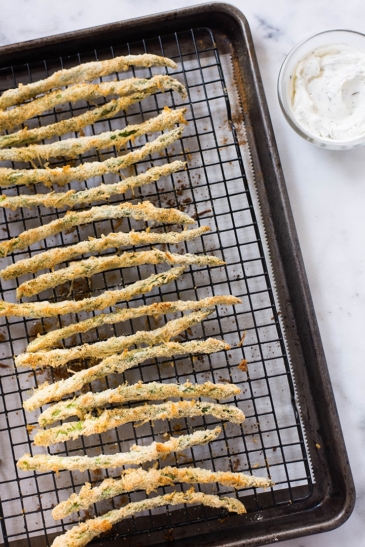 An overhead image of freshly made Oven Baked Parmesan Asparagus Fries on a baking sheet, made with fresh asparagus, almond meal, chickpea flour, grated parmesan, eggs, black pepper and sea salt.