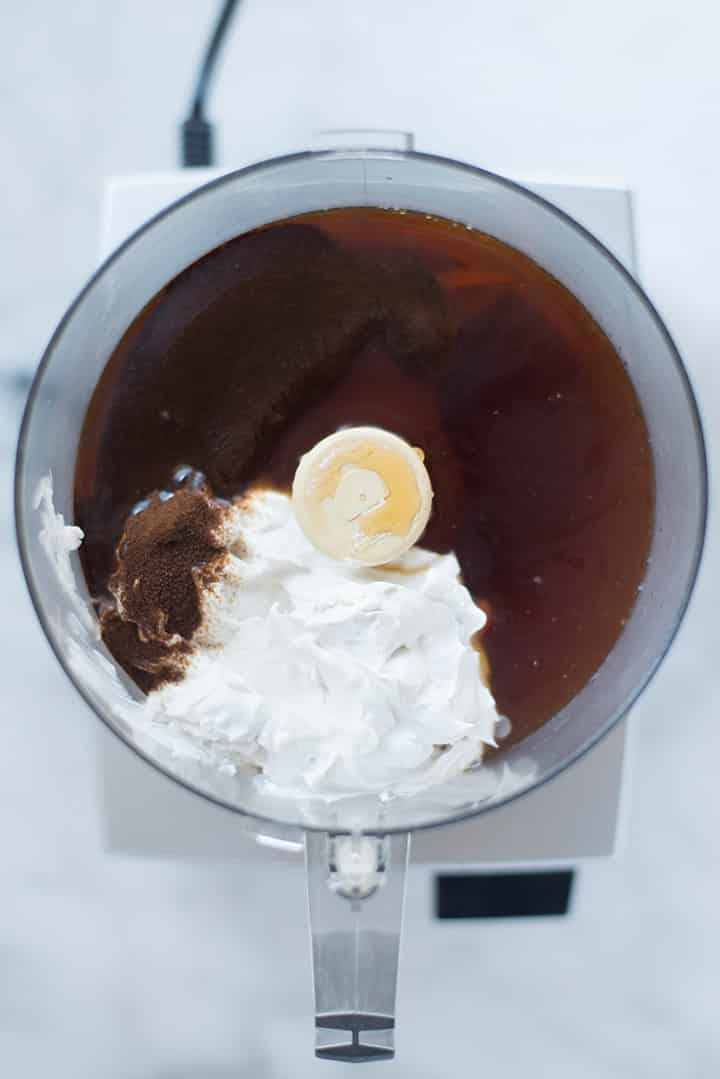 An overhead image of a blender with all the ingredients for Coffee Ice Cream including full fat coconut milk, pure maple syrup, brewed and chilled strong coffee, instant coffee and vanilla extract.