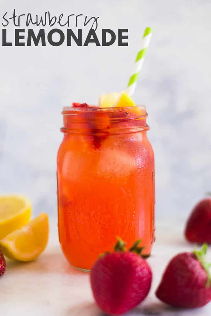 A side image of a mason jar filled with Easy Homemade Strawberry Lemonade made from fresh strawberries, freshly squeezed lemon juice, water and raw honey, served with fresh strawberries, ice cubes and a slice of lemon.