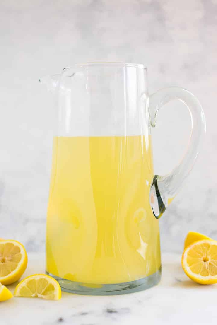 A side image of a pitcher on a kitchen counter half-filled with the basic Homemade Lemonade made with freshly squeezed lemon juice, water and raw honey.