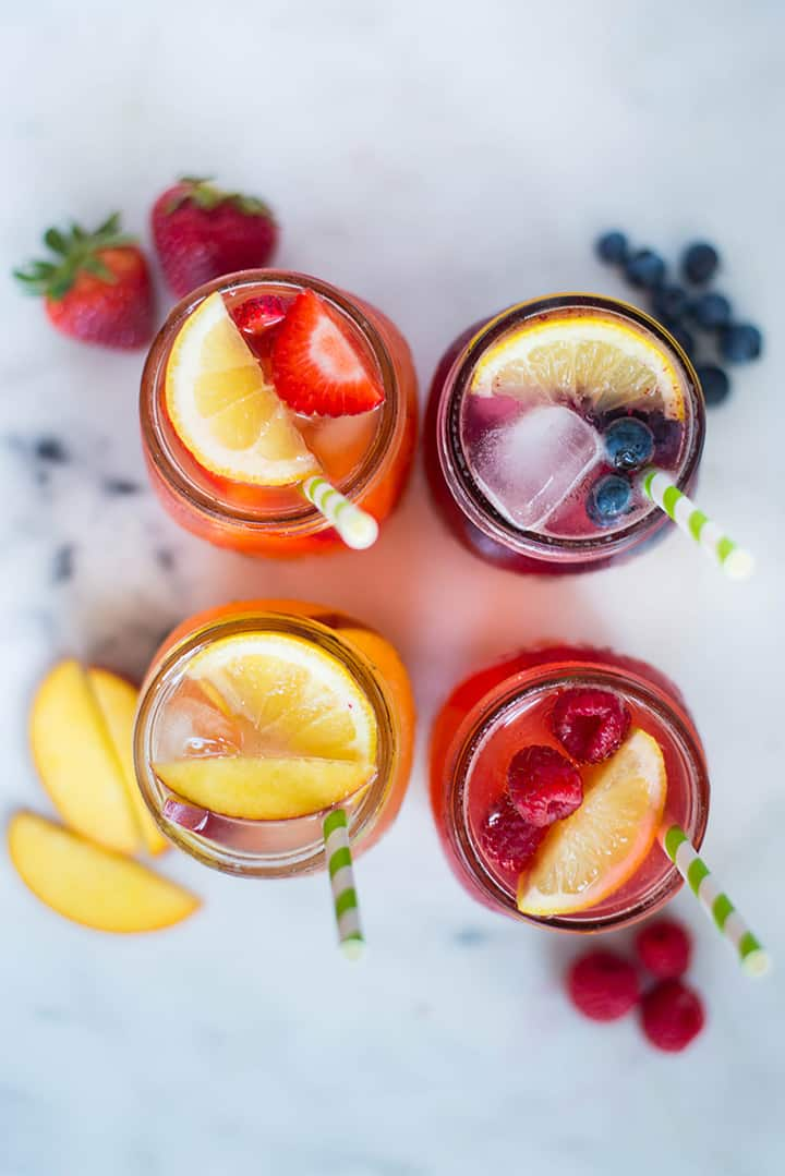 An overhead image of four mason jars on a kitchen counter each filled with Homemade Lemonade including Raspberry Lemonade, served with ice cubes, fresh raspberries and a slice of lemon, Peach lemonade, served with ice cubes, fresh peach slices and a slice of lemon, Strawberry Lemonade, served with ice cubes, lemon slices and fresh strawberries and Blueberry Lemonade served with ice cubes, a slice of lemon and fresh blueberries.