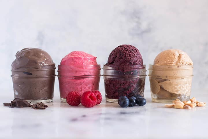 A side image of four glass dessert bowls lined up on a kitchen counter each with one of the 4 different-flavored frozen yogurts including Chocolate Frozen Yogurt, Raspberry Frozen Yogurt, Blueberry Frozen Yogurt and Peanut Butter Frozen Yogurt.