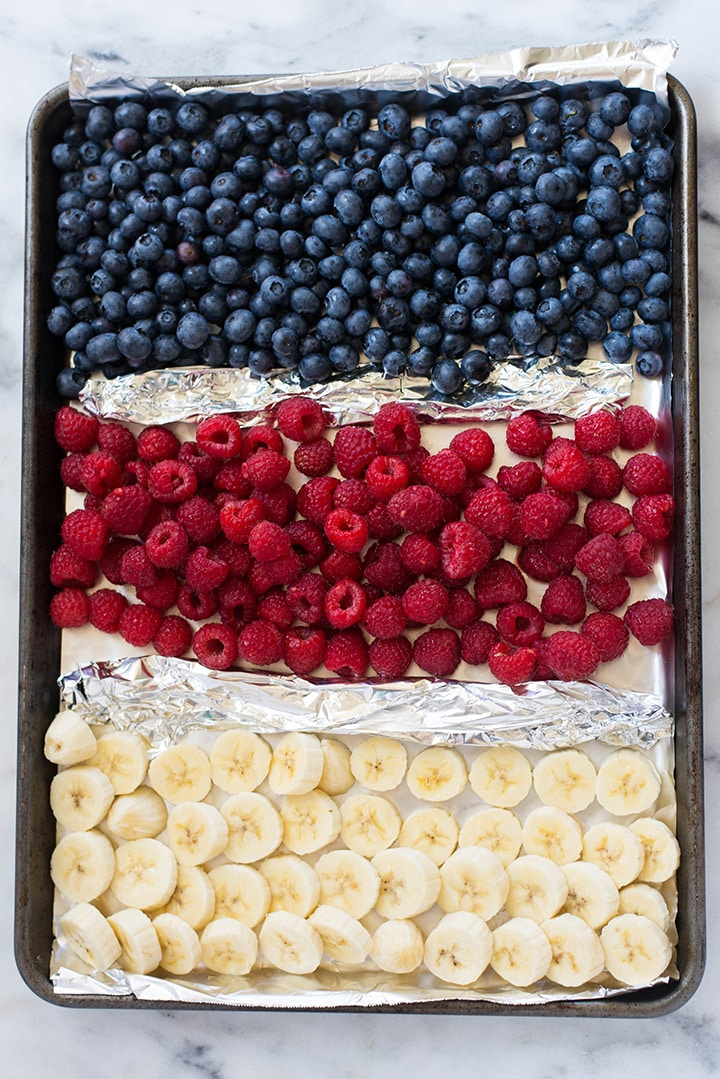 An overhead image of a baking tray with fresh blueberries, raspberries and banana slices ready to be placed in the freezer for the Frozen Yogurt recipes.