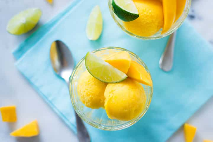 A close up image of a glass serving bowl with two scoops of Mango Sorbet, served with fresh mango slices and a slice of lime.