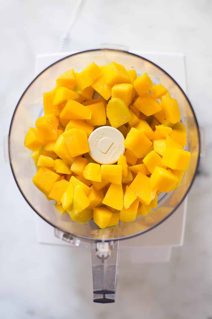 An overhead image of frozen diced mango in a food processor ready to be blended into Mango Sorbet.