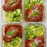 An close up image of four glass containers each with one serving of Healthy Chicken Parmesan served over zucchini noodles ready for meal prep.