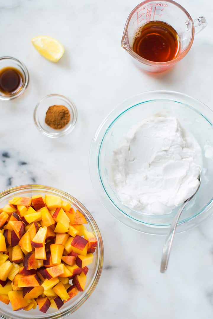 An overhead image of the kitchen counter with all the ingredients for Peach Ice Cream including ripe peaches, full-fat coconut milk, vanilla extract, maple syrup, lemon juice and cinnamon.