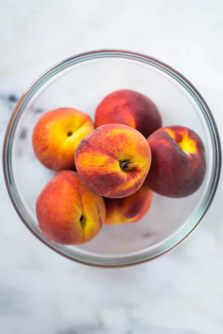 An overhead image of a glass bowl with 5 whole peaches for the Peach Ice Cream on a kitchen counter.