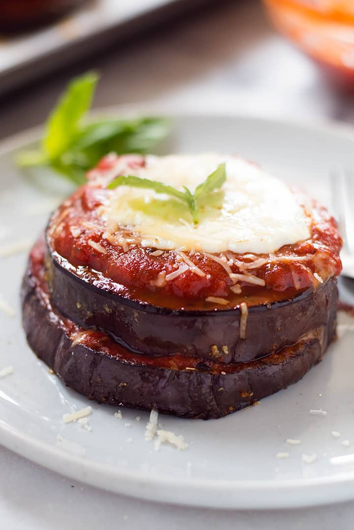 A close up image of a single serving of Baked Eggplant Parmesan made with roasted eggplant, homemade tomato sauce, mozzarella and grated parmesan.