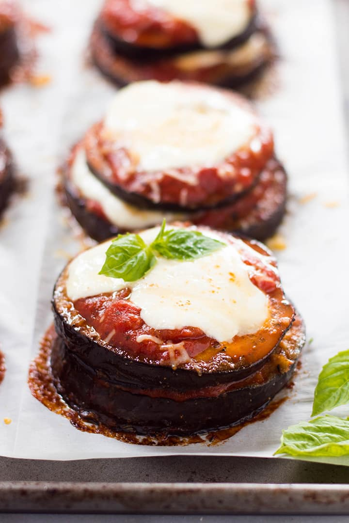A side image of Baked Eggplant Parmesan made with roasted eggplant, homemade tomato sauce, mozzarella and grated parmesan.