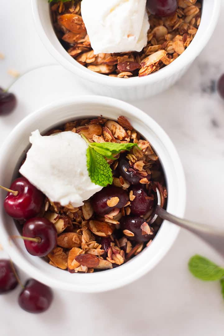 An overhead image of two servings of freshly baked Summer Cherry Crisp, topped with plain greek yogurt and decorated with fresh mint.