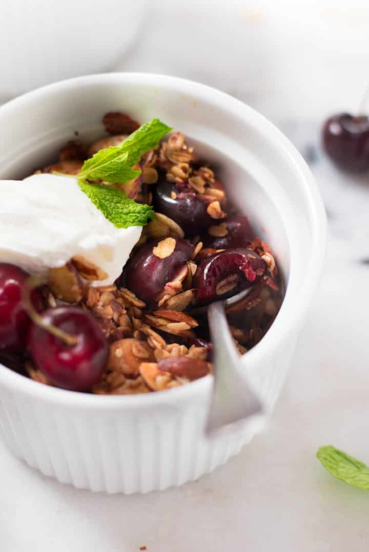 A side close up image of a ramekin with baked Summer Cherry Crisp, served with a dollop of plain Greek yogurt and decorated with fresh mint.
