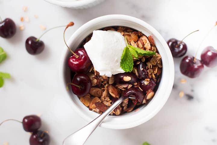 An overhead image of a single serving of Summer Cherry Crisp on a kitchen counter, served with a dollop of plain Greek yogurt and decorated with fresh mint.