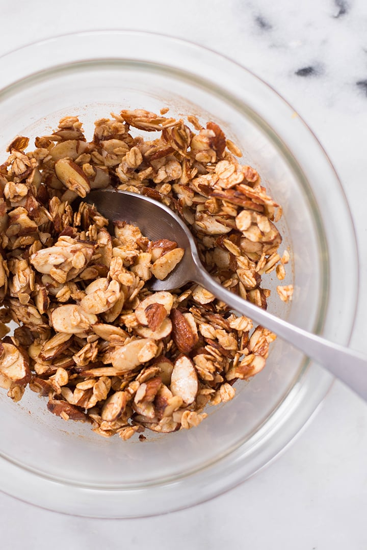 An overhead image of a glass bowl with sliced almonds, rolled oats, pure maple syrup, coconut oil, ground cinnamon, ground ginger and sea salt for the Crisp Topping.