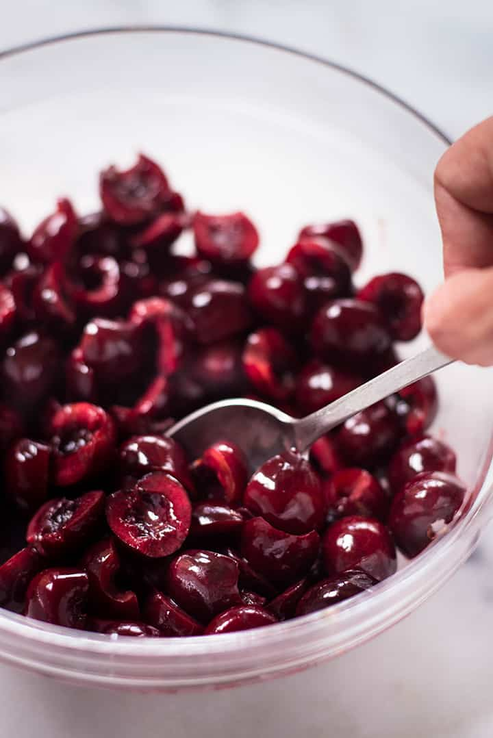 A close up image of a glass bowl with fresh pitted cherries for the Summer Cherry Crisp.
