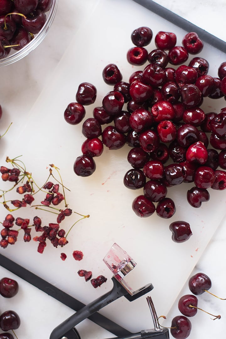 An overhead image of a baking tray with fresh pitted cherries for the Summer Cherry Crisp.