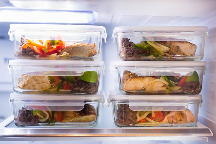 A side image of 6 meal prep containers with Healthy Chicken Fajitas, made with Fajita Chicken, Fajita Bell Peppers and Lime & Cilantro Black Beans stored in the fridge.