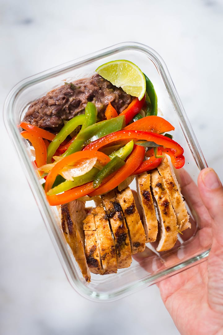 An overhead image of a meal prep container with Healthy Chicken Fajitas made with Fajita Chicken, Fajita Bell Peppers and Lime & Cilantro Black Beans ready to be stored in the fridge.