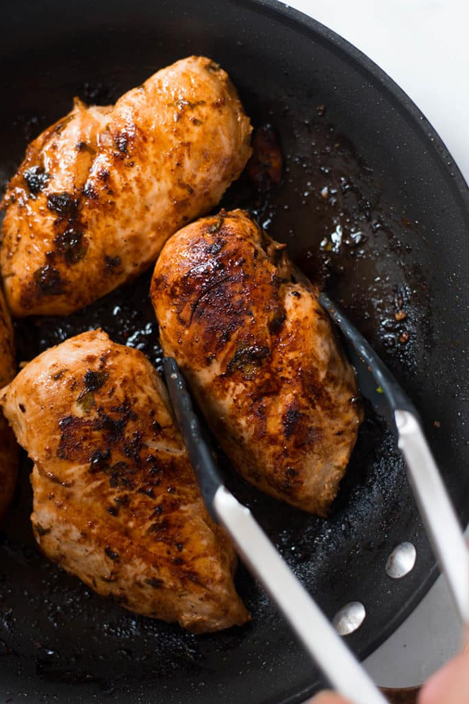 Close up view of a skillet with browned chicken, one piece being picked up with tongs.