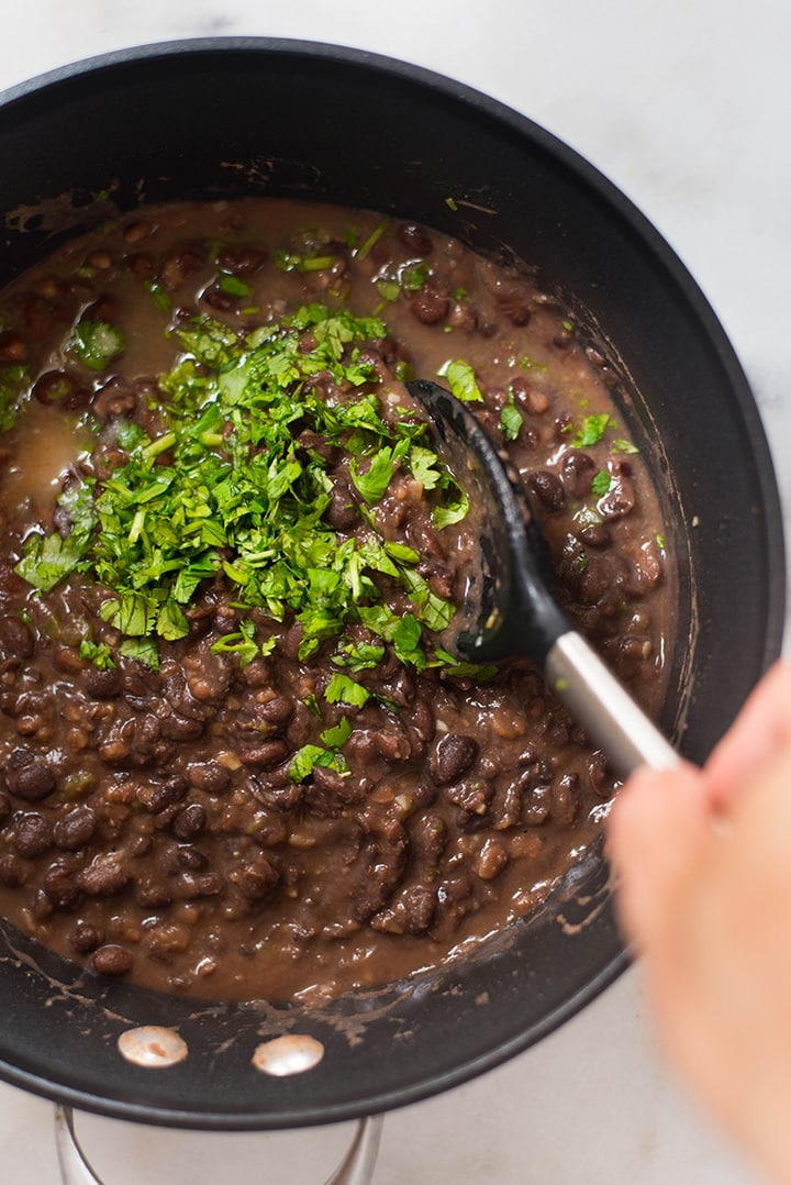 An overhead image of a spoon stirring Lime and Cilantro Black Beans in a pan, made with canned low sodium black beans, jalapeno, low sodium chicken broth, garlic, fresh cilantro, olive oil, sea salt, cumin and lime juice.
