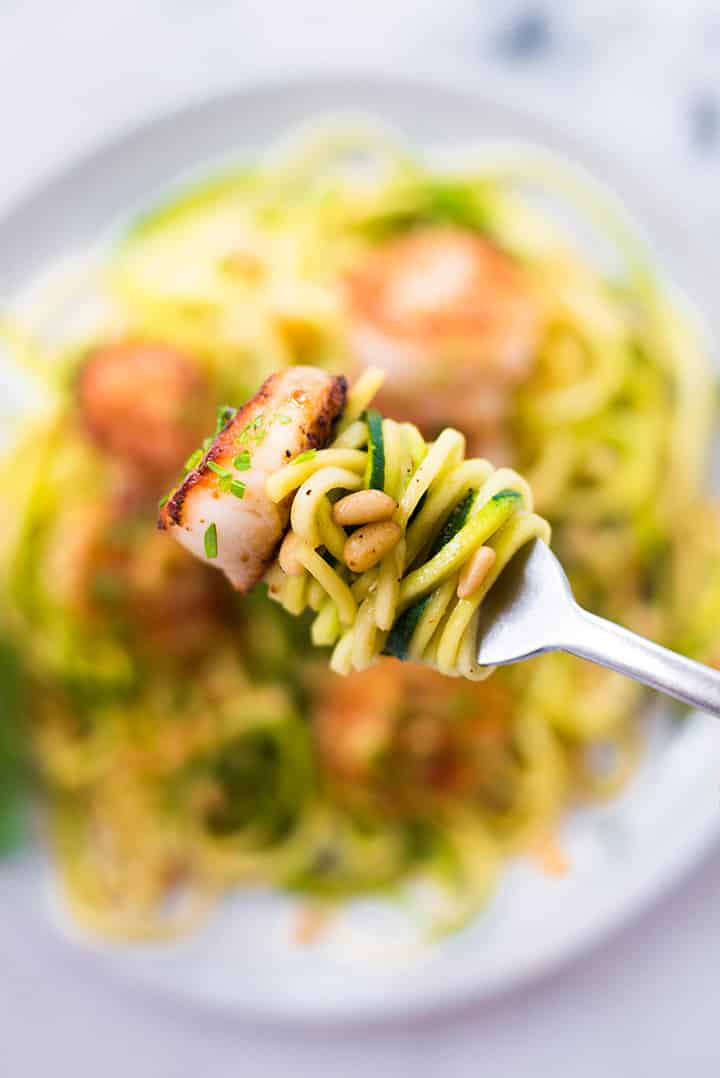 Close up of pan seared scallops and zucchini noodles wrapped around a fork ready o be eaten. You can also see the roasted pine nuts used to top the zucchini noodles.